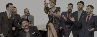 The Hot Sardines band popping a bottle of champagne on top of a piano