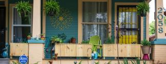 Front porch with hanging plants and a yellow door