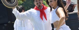 man in white with red scarf holding traditional Colombian hat, woman dancer next to him