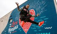 Lil Buck dancing in front of the I Love Memphis mural near Crosstown Concourse